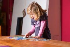Kleines Mädchen, das ein Puzzlen tut Stockbild