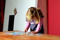 Kleines Mädchen, das ein Puzzlen tut Stockfotos