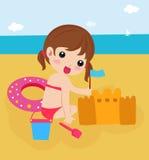 Kleines Mädchen, das ein Sandschloß am Strand aufbaut Stockfoto