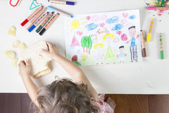 Kleines Mädchen, das ein Sandwich nach der Fertigung ihres Familie drawi fängt Stockfotos