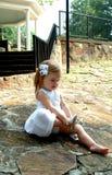 Kleines Mädchen, das ein Schuhe setzt Lizenzfreie Stockbilder