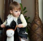 Kleines Mädchen, das ein Spielzeugpferd reitet Lizenzfreies Stockfoto