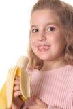 Kleines Mädchen, das eine Banane isst Stockfoto
