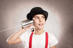 Kleines Mädchen, das eine Dose als Telefon verwendet Stockbild