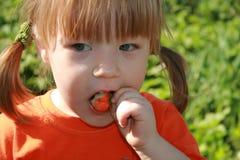 Kleines Mädchen, das eine Erdbeere isst Stockbild