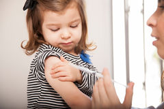 Kleines Mädchen, das eine Grippeimpfung erhält Stockfotos