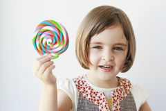 Kleines Mädchen, das eine große Süßigkeit anhält stockbild