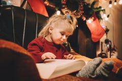 Kleines Mädchen, das eine Gutenachtgeschichte durch den Kamin liest Lizenzfreie Stockfotos