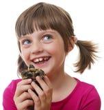 kleines Mädchen, das eine Haustierschildkröte hält Lizenzfreies Stockfoto