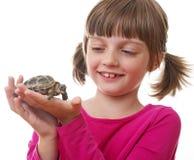 kleines Mädchen, das eine Haustierschildkröte hält Stockbilder