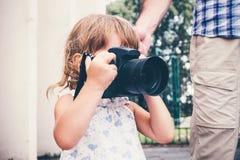 Kleines Mädchen, das eine Kamera hält und Fotos macht Stockfoto