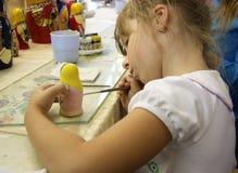 Kleines Mädchen, das eine matrioshka Russepuppe malt Stockfotos
