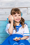 Kleines Mädchen, das eine Muschel und Lachen hält Lizenzfreies Stockfoto
