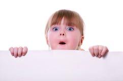 Kleines Mädchen, das eine Pappe schaut überrascht anhält Stockfotografie