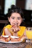 Kleines Mädchen, das eine Pizzascheibe isst lizenzfreie stockfotos