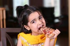 Kleines Mädchen, das eine Pizzascheibe isst Lizenzfreie Stockfotografie