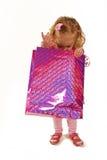Kleines Mädchen, das eine rosafarbene Einkaufstasche untersucht Lizenzfreie Stockbilder