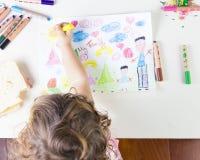 Kleines Mädchen, das eine Sonne in einem Kinderzeichnen von ethnisch gemischtem Fam malt Stockfoto