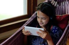 Kleines Mädchen, das eine Tablette in einer Hängematte verwendet Stockfotografie