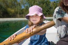 Kleines Mädchen, das in einem Bootsschauen schaufelt Lizenzfreie Stockbilder