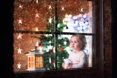 Kleines Mädchen, das an einem Fenster auf Weihnachtsabend sitzt Stockfotografie