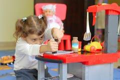 Kleines Mädchen, das in einem Kindergarten spielt Stockfotografie