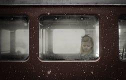 Kleines Mädchen, das in einem roten Schienenfahrzeugfenster mit dem Winterschneefallen denkt Stockbilder