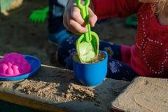 Kleines Mädchen, das in einem Sandkasten mit einer Plastikschaufel und einem Becher spielt Stockfotos