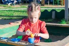 Kleines Mädchen, das in einem Sandkasten mit einer Plastikschaufel und einem Becher spielt Lizenzfreie Stockfotos