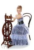 Kleines Mädchen, das an einem Spinnrad sitzt lizenzfreies stockfoto