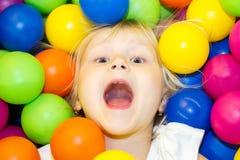 Kleines Mädchen, das in einem Stapel von farbigen Bällen liegt Lizenzfreie Stockfotos