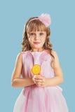 Kleines Mädchen, das in einem Studio über Farbhintergrund aufwirft Halten von a Lizenzfreies Stockfoto