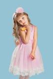 Kleines Mädchen, das in einem Studio über Farbhintergrund aufwirft Halten von a Stockbild
