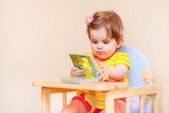 Kleines Mädchen, das an einem Tisch vor Buch sitzt stockbild
