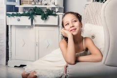 Kleines Mädchen, das in einem Wohnzimmer sitzt Lizenzfreie Stockbilder