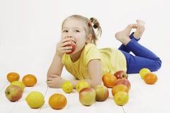Kleines Mädchen, das einen Apfel beißt Stockbilder