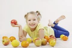 Kleines Mädchen, das einen Apfel isst Stockbilder