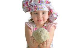 Kleines Mädchen, das einen Ball des Teigs hält Lizenzfreie Stockfotos