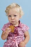 Kleines Mädchen, das einen Biskuit isst. lizenzfreie stockbilder