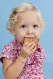 Kleines Mädchen, das einen Biskuit isst. lizenzfreies stockbild