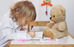 Kleines Mädchen, das einen Doktor mit ihrem Teddybären spielt lizenzfreie stockbilder