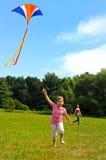 Kleines Mädchen, das einen Drachen fliegt Stockbild