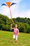 Kleines Mädchen, das einen Drachen fliegt Lizenzfreie Stockfotos