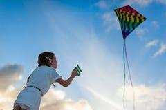 Kleines Mädchen, das einen Drachen fliegt Stockfoto
