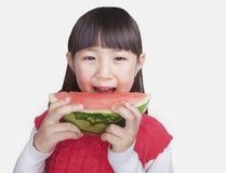 Kleines Mädchen, das einen enormen Biss aus einer Wassermelone heraus, Kamera betrachtend, Atelieraufnahme nimmt Stockbilder