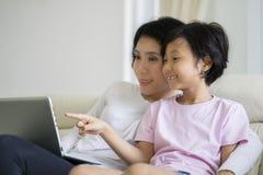 Kleines Mädchen, das einen Film mit ihrer Mutter aufpasst Stockfotos