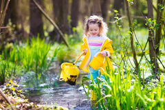 Kleines Mädchen, das einen Frosch abfängt Stockbild