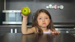 Kleines Mädchen, das einen grünen Apfel und ein Lächeln isst stock footage