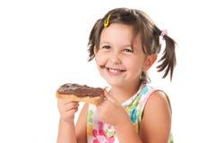 Kleines Mädchen, das einen Imbiß beißt Stockbilder