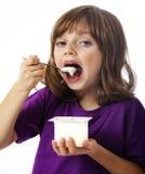 Kleines Mädchen, das einen Joghurt isst Lizenzfreie Stockbilder
